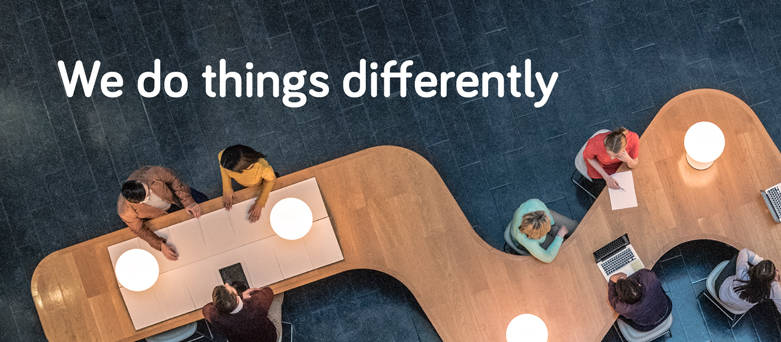 Birds eye view of people working at a zig-zag desk with the words We do things differently