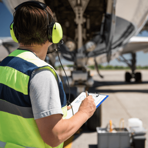 Man with clipboard in front of airplane